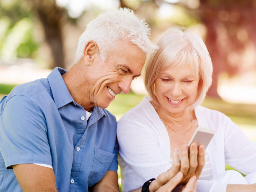 couple over 70 on a date looks at the phone